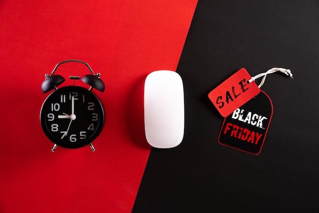 Черная пятница продажа текст с будильником, белая мышь на красном черном фоне. Premium Фотографии