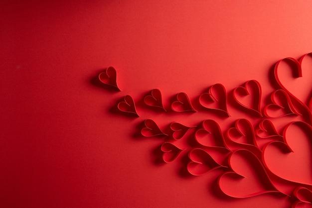 赤い背景の赤い紙の心。愛とバレンタインデーのコンセプト。 Premium写真
