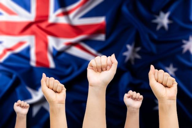 オーストラリアの日の概念。バックグラウンドでオーストラリアの旗を持つ人々の手。 Premium写真
