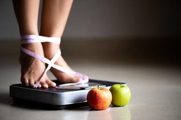 測定テープと青リンゴで体重計を踏む女性の脚。 Premium写真