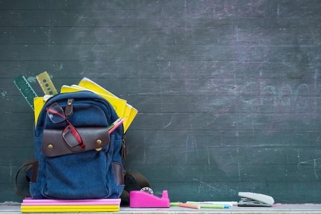 学校のバックパックと学校用品、黒板の背景。 Premium写真
