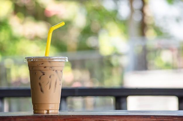 木製のテーブルの上のグラスにアイスコーヒー。 Premium写真