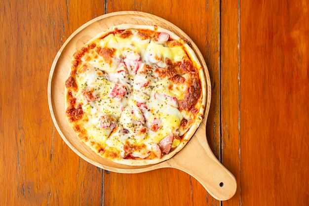 Пицца с ветчиной на деревянном подносе ставится на стол. Premium Фотографии