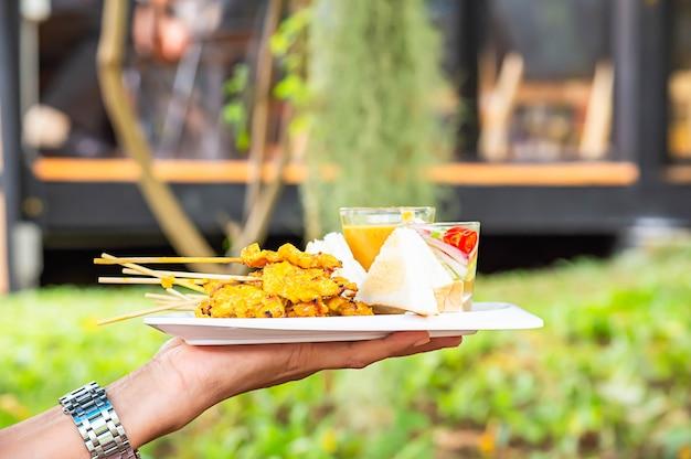 ココナッツミルクと白いプラスチックプレートに手でピーナッツディップソースとパンと豚肉のサテ。 Premium写真
