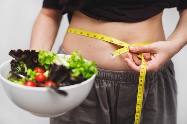 Женщина, измеряющая ее живот и вес Бесплатные Фотографии