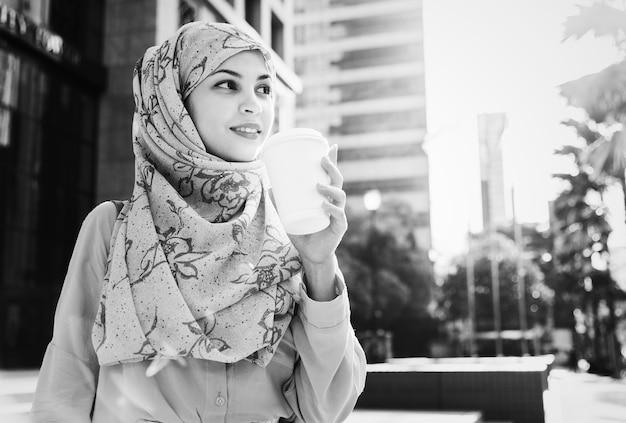 都市でコーヒーを飲むイスラムの女性 無料写真