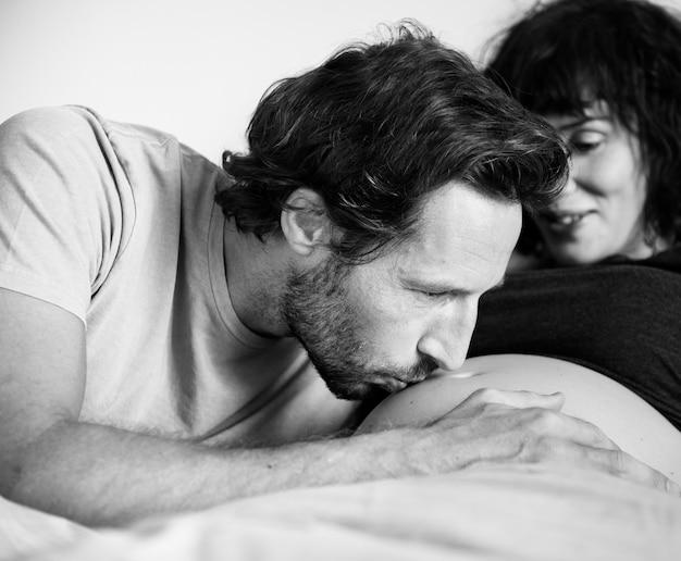 赤ちゃんのバンプにキスする夫 無料写真