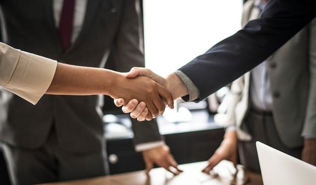 会議室で握手をするビジネスマン 無料写真