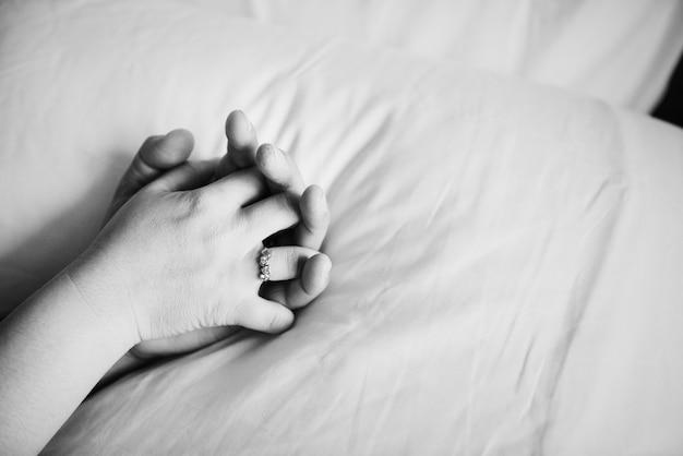 Пара, держась за руки на кровати Бесплатные Фотографии