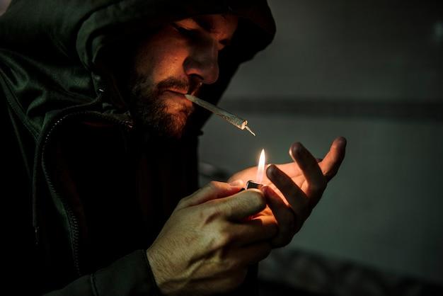 Бездомный человек, курящий зависимость от сигарет Premium Фотографии