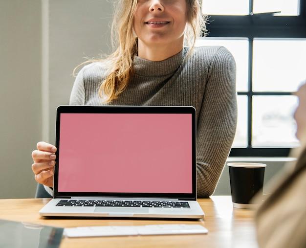 ラップトップの画面を指しているブロンドの女性 無料写真