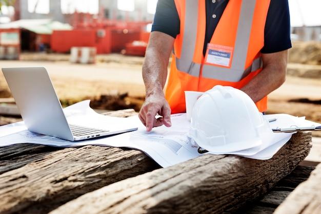木製の寝台の計画を指している建設現場の請負業者の拡大写真 無料写真