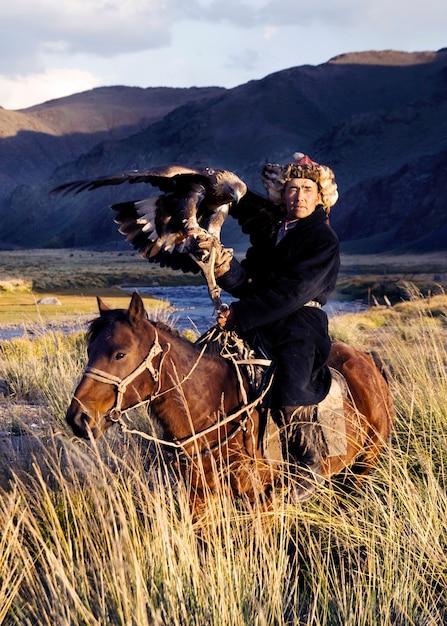 カザフスタンの男性は、伝統的に狐とオオカミを訓練されたゴールデンワシを使って狩る。西モンゴルのオルゲイ。 無料写真