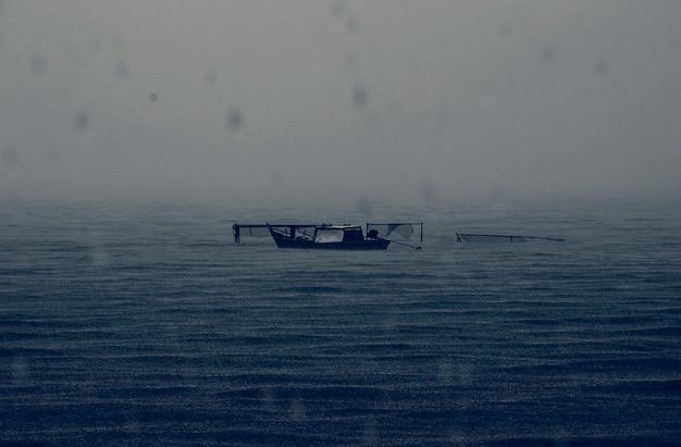 放棄されたボート雨の多い暗い海 無料写真