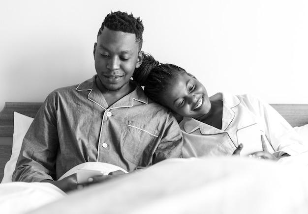ベッドで携帯電話を使う幸せな夫婦 無料写真