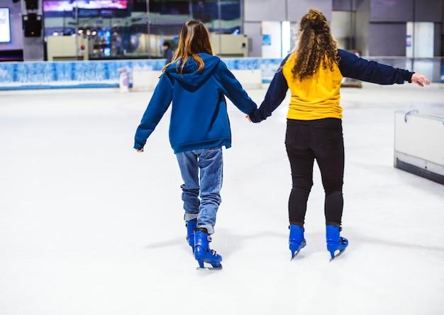 女の子の友達のアイススケートリンク 無料写真