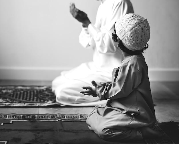 ドゥアをアッラーにする方法を学ぶムスリムの少年 無料写真