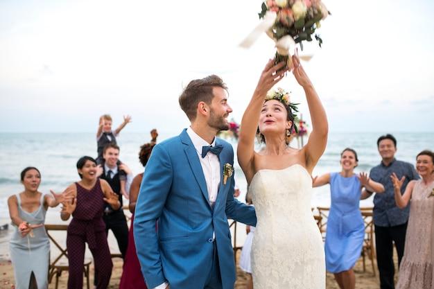 ビーチでの結婚式の若いカップル Premium写真