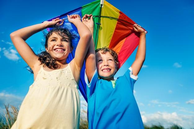小さな女の子と一緒にカイトを遊ぶリトルボーイ Premium写真