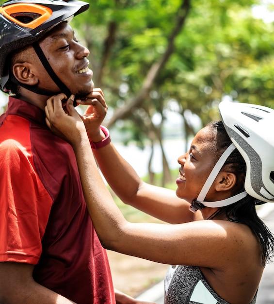 女性は彼女のボーイフレンドのために自転車のヘルメットを締める 無料写真