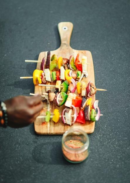 ビーガンバーベキュー串に調味料を加える料理 無料写真