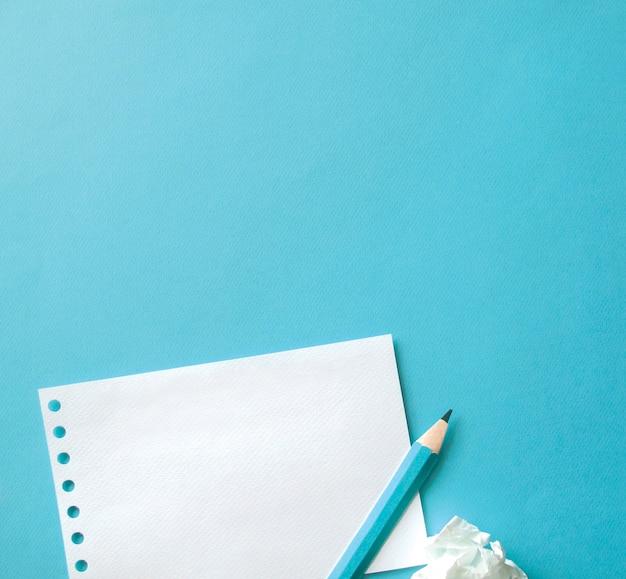 青い背景の紙とペンのシート 無料写真
