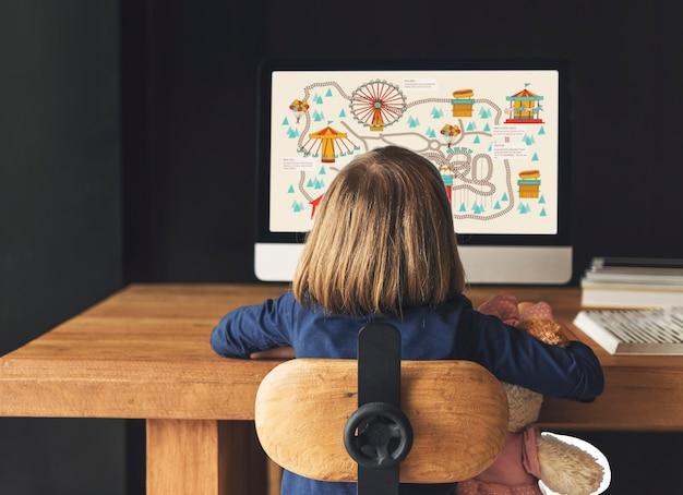 Маленькая девочка, играющая на компьютере Premium Фотографии