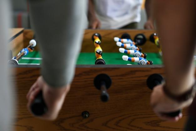 フーズボールテーブルサッカーゲームレクリエーションレジャーを楽しむ人々 無料写真