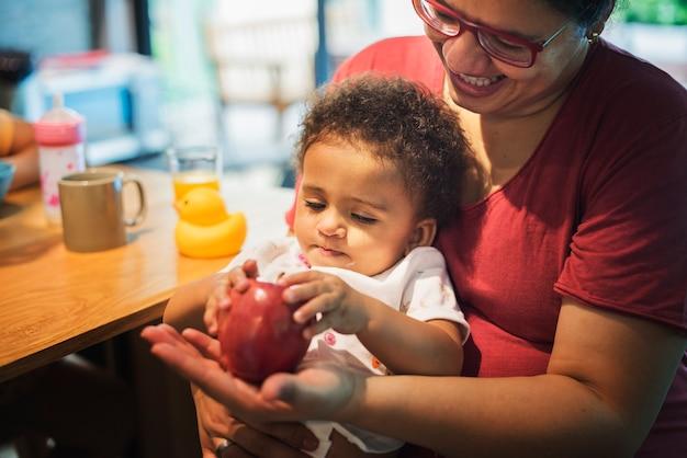 Мама, позволяющая дочери играть с яблоком Бесплатные Фотографии