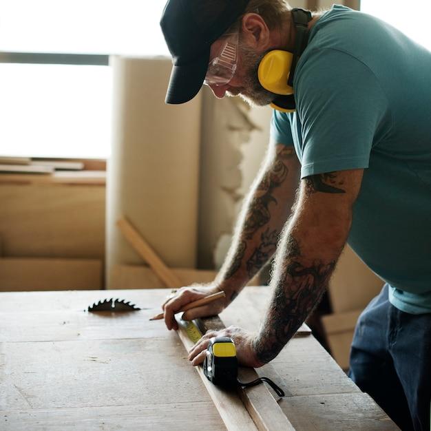 木材の鉛筆と測定テープを使用して大工 無料写真
