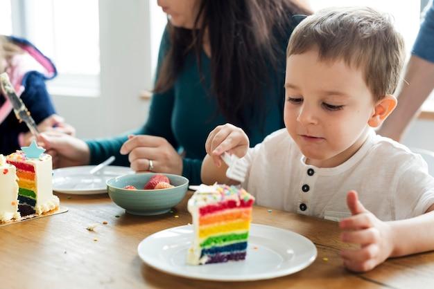 虹色のケーキを食べる小さな男の子 無料写真