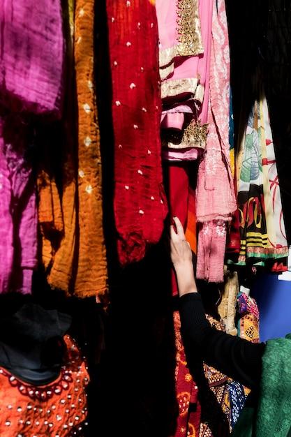 市場でカラフルなサリーを選ぶ女性 無料写真