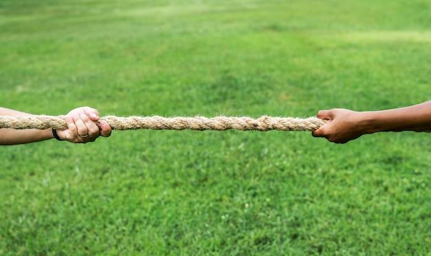戦争ゲームの綱引きでロープを引っ張る手の拡大 Premium写真