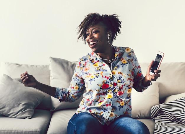 自宅で音楽を楽しむアフリカ系アメリカ人女性 Premium写真