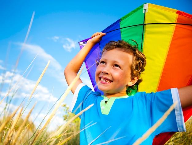 屋外で凧を演奏する陽気な若い少年 Premium写真