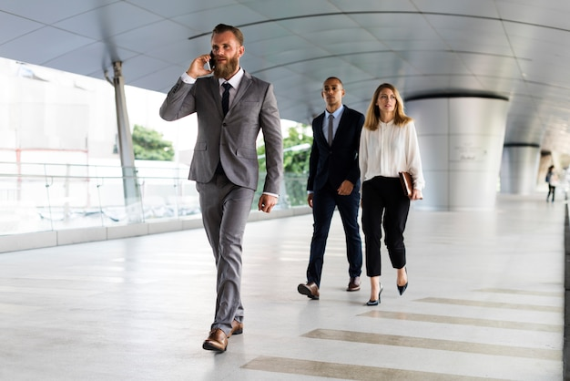 ビジネスマン、電話、ビジネスマン、彼の後ろを歩く Premium写真