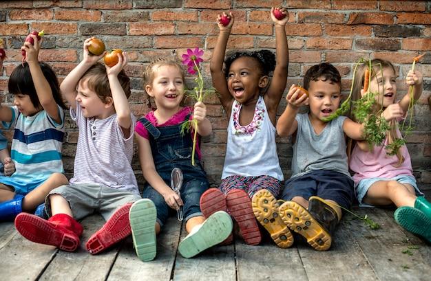 新鮮な野菜と一緒に座っている多様な子供のグループ Premium写真