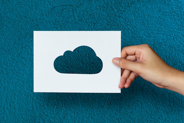 青い背景と手の雲の紙の彫刻を保持する 無料写真