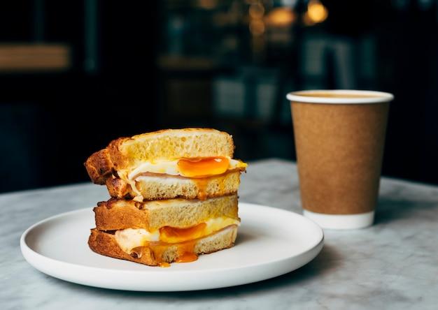 テーブル上のサンドイッチとコーヒーのカップ 無料写真