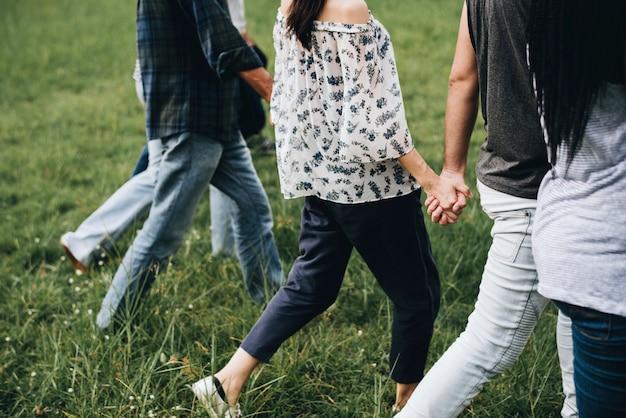 多様な人々が手を持って公園で走っています 無料写真