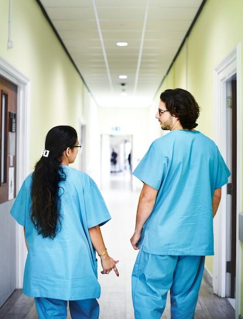 病院の廊下を歩いている同僚 無料写真