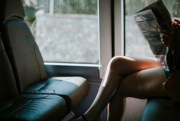 バスでニュースを読んでいる女性 無料写真
