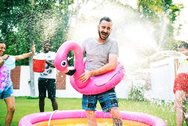 夏の時間を楽しんで水を吹き飛ばしている様々なグループの友達 無料写真