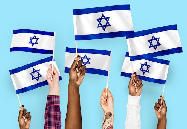 イスラエルの旗を振る手 無料写真
