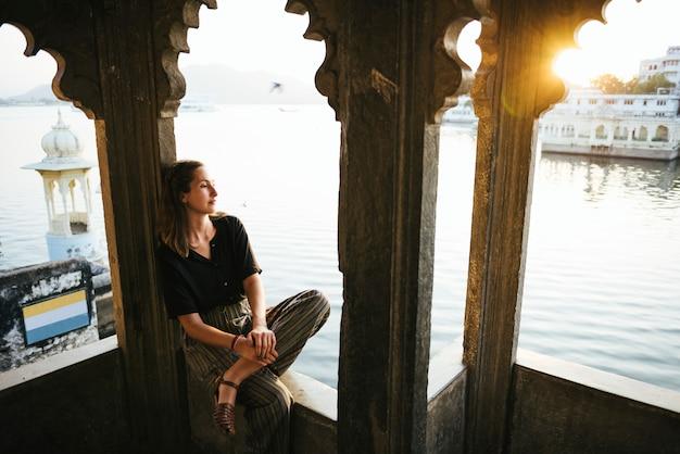 インド、ウダイプールの文化的建築物に座っている西洋の女性 無料写真