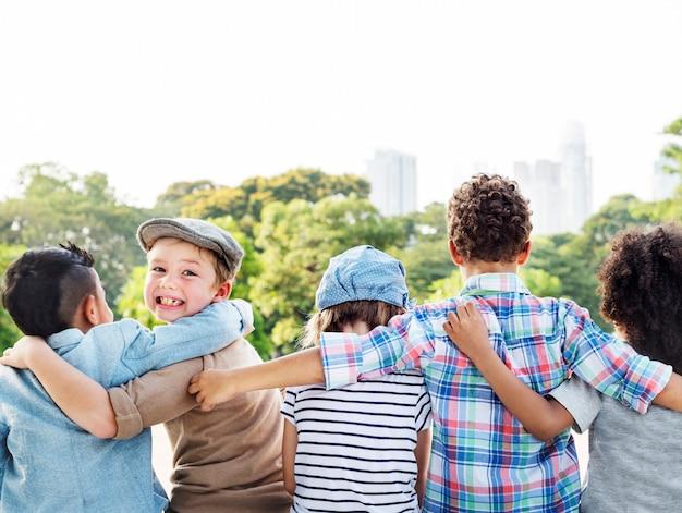 多様な子供たちのグループが一緒に腕を回した 無料写真