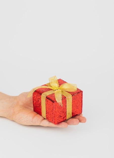 手、ゴールデン・リボンの赤いギフト・ボックス 無料写真