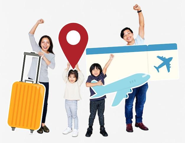 Веселая семья держит значки путешествия и билет Бесплатные Фотографии
