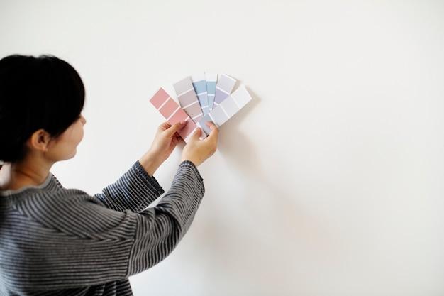 アジアの女性が壁の色を選ぶ Premium写真