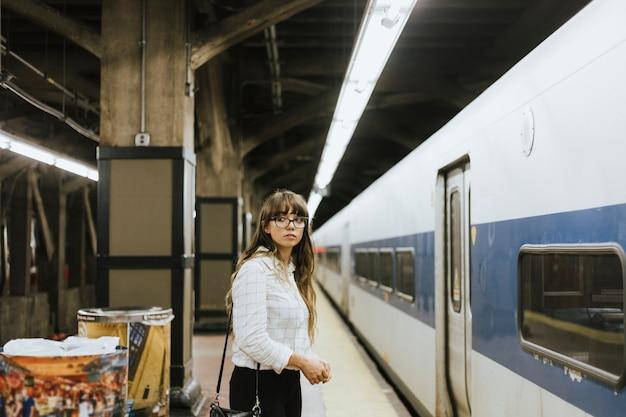 地下鉄のプラットフォームで電車を待っている思いやりのある女性 Premium写真